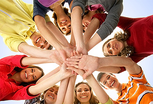 A group of young adults stacking their open hands to imply teamwork.